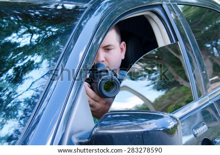 Private investigator on a stakeout is photographing the situation to document the events.  - stock photo