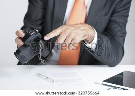 private investigator showing proof on a camera display - stock photo