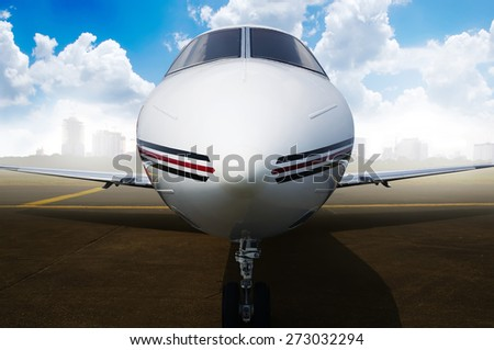 Private jet airplane parking at the airport. With city and blue sky background - stock photo