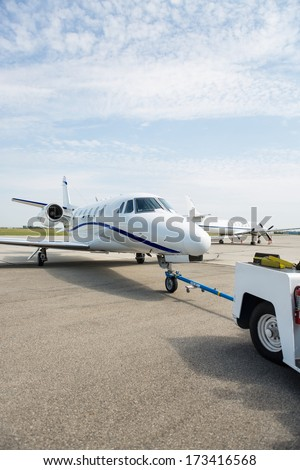 Private jet being towed by an airport vehicle - stock photo