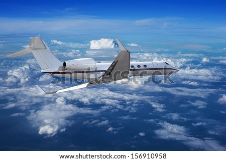 Private jet cruising above the clouds - stock photo