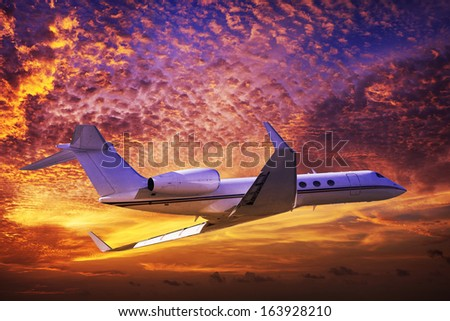 Private jet cruising in a sunset sky - stock photo