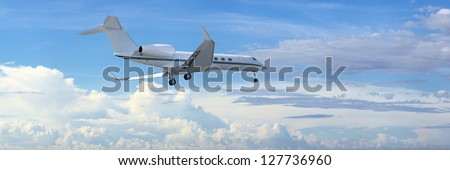 Private jet is maneuvering for landing in a cloudy sky. Panoramic composition. - stock photo