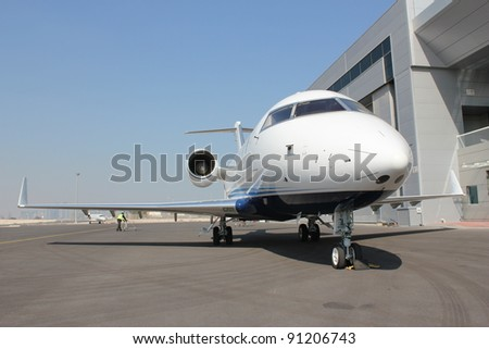 Private jet parked outside hanger