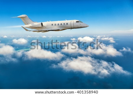 Private jet plane flying above clouds - stock photo
