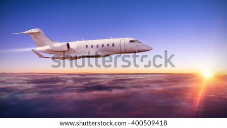 Private jet plane flying above clouds in dramatic sunset light - stock photo