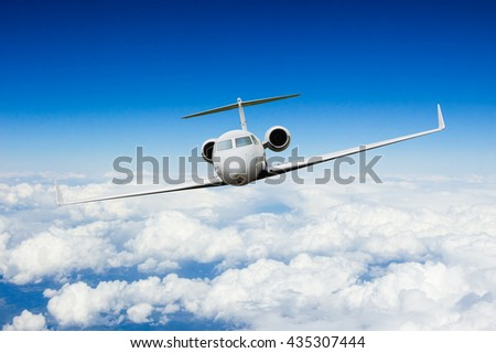 Private jet plane flying above clouds, shot from front view - stock photo