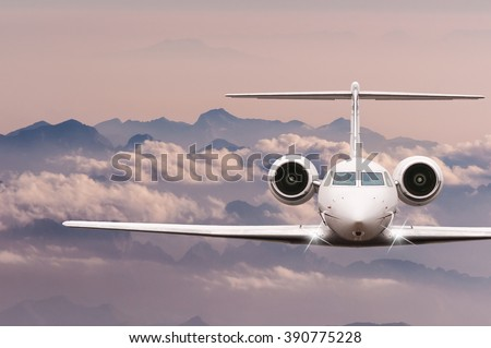 Private Jet plane over clouds and Alps mountain on sunset. Front view of a big passenger or cargo aircraft, business jet, airline. Travel concept. Empty space for text - stock photo