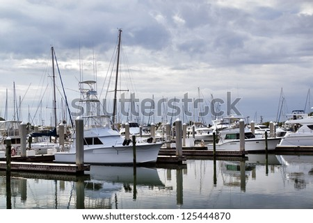 Private luxury yachts and sailboats at the Port Canaveral, harbor and docks as a mid-afternoon Florida storm builds overhead. The water in the harbor is glassy, mirroring the boats at their moorings. - stock photo