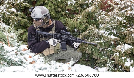 Private military contractor PMC with assault rifle in the winter forest - stock photo