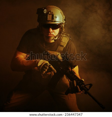 Private military contractor PMC with assault rifle on dark background