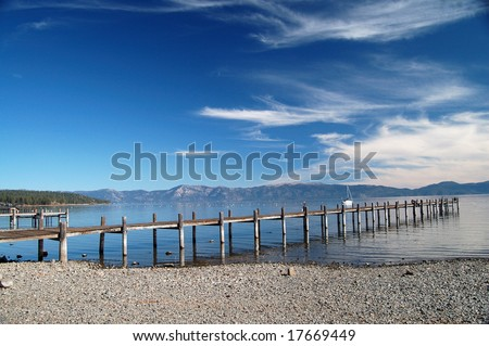 Private pier into the water of Lake tahoe on a clear day with blue sky - stock photo