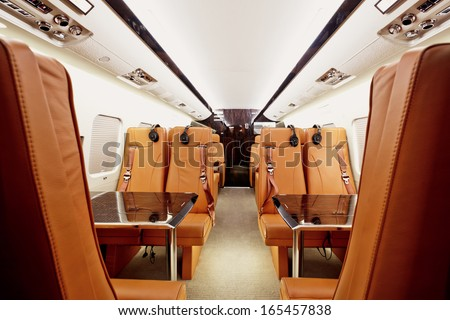 Private plane interior with wooden tables and leather seats - stock photo