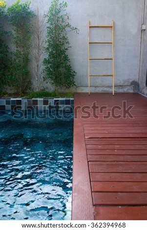 Private pool with blue mosaic tiles with red planks in the garden.