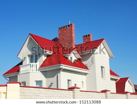 Private residence with a red roof against the blue sky - stock photo
