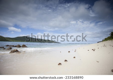 Private Secluded Beach In The Caribbean Sea With Clouds, Blue Skies, Clear Blue Water, And White Sand Beaches - stock photo