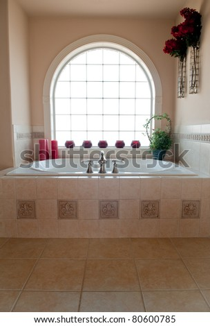 Private whirlpool bath below an arched, glass block window.