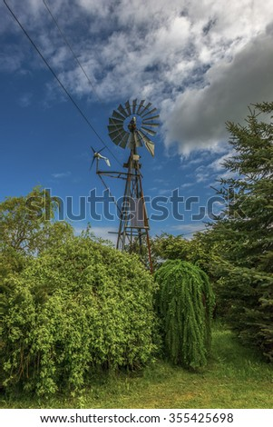 Private wind generator next to an ancient exhaust fuel generator.Focus is on windmill.