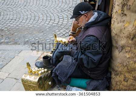 PRIZREN, KOSOVO - APRIL 19, 2015: A shoe shiner works in a street of the old town. Prizren, the cultural capital of Kosovo, is a pretty city of mosques and monasteries dating to the 14th century.