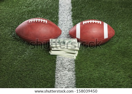 Pro and college style footballs with a pile of money on the line - stock photo