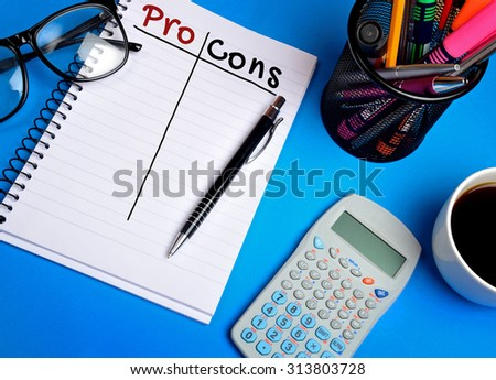 Pro Cons word on notebook on blue background
