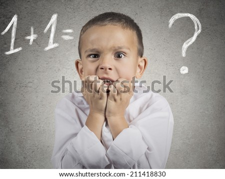Problem. Closeup portrait anxious, funny looking boy, trying to solve math assignment, isolated grey wall background. Human face expressions, emotions, feelings, body language, life perception - stock photo