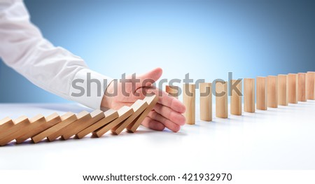 Problem Solving - Hand Stopping Domino Effect  - stock photo