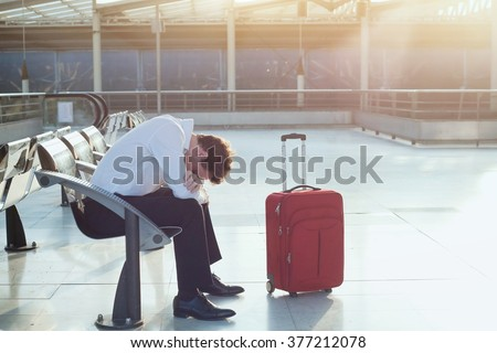 problem with transportation, delay of flight, depressed commuter with his luggage - stock photo