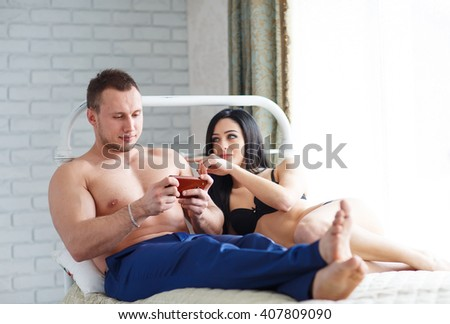 Problems in the family. Angry young woman lying on the bed, against her husband, who plays the game on the phone. - stock photo