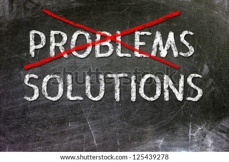 Problems Solutions handwritten with white chalk on a blackboard. - stock photo