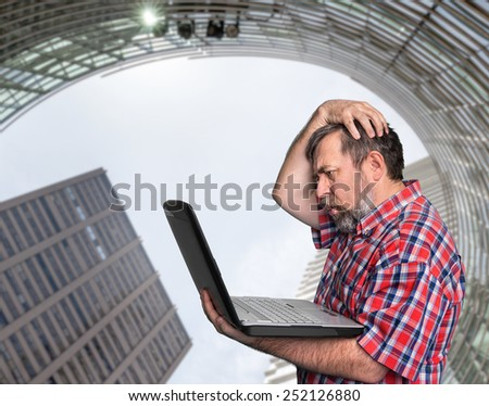 Problems with computer. Middle aged stressed businessman working on laptop against urban background - stock photo