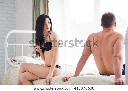 Problems with honeymooners. Couple sitting on the bed facing away. - stock photo