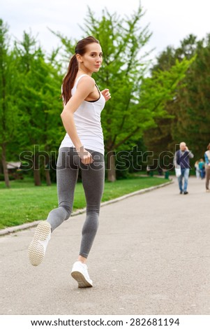 Process is important. Youthful woman is practicing running in green park - stock photo