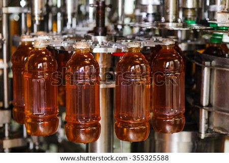 process of bottling on production line - stock photo