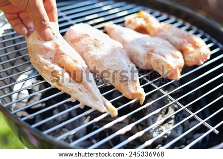 Process of cooking raw spicy chicken fillet on grill - stock photo