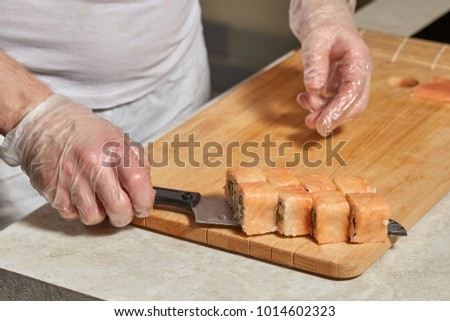 Process of making sushi. Chef hands preparing rolls with salmon on wooden board