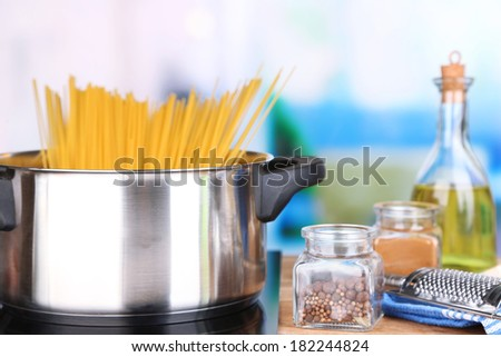 Process of preparing pasta. Composition with row spaghetti in pan, grater, cheese, on wooden table  on bright background - stock photo