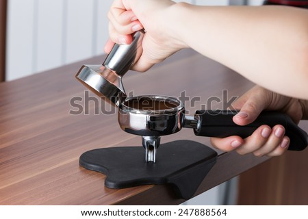 Process of tamping the coffee for espresso preparation - stock photo