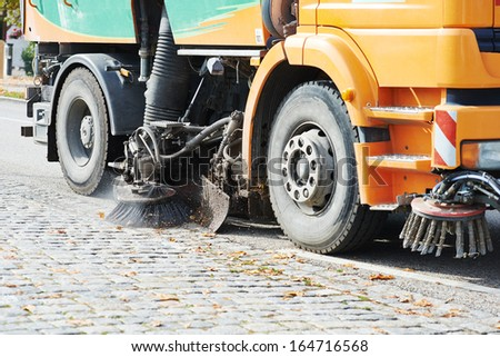 Process of urban street cleaning. Municipal machanical truck - stock photo