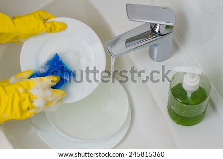 process of washing dishes in yellow gloves - stock photo