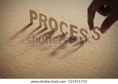 PROCESS wood word on compressed board with human's finger at S letter
