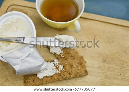 Processes cheese and table knife next to yellow tea cup