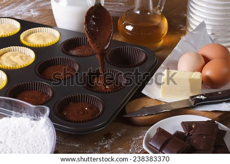 processes of preparation of chocolate muffins close-up on the table. horizontal  - stock photo