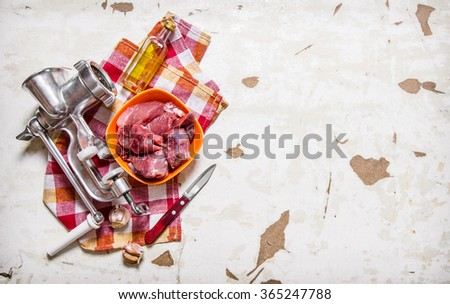 Processing of meat. Raw fresh meat with a meat grinder . On rustic background. Free space for text . Top view - stock photo
