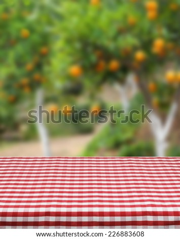 Product photo template red table cloth orange grove background - stock photo