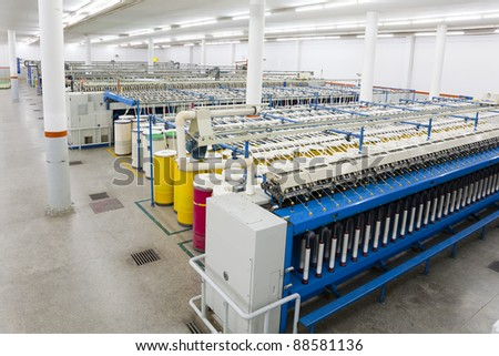 production hall of a spinning a weaving machines in a textile mill, textile factory, yarn manufacturing