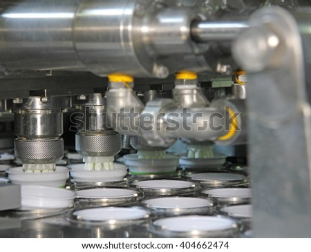Production of yogurt in a dairy factory, industrial equipment for filling in plastic cups - stock photo