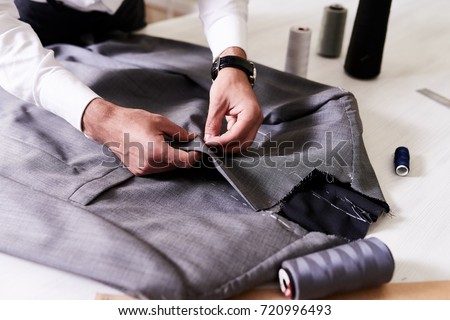 Production process of custom-made male jacket: unrecognizable tailor concentrated on sewing with needle and thread, close-up shot