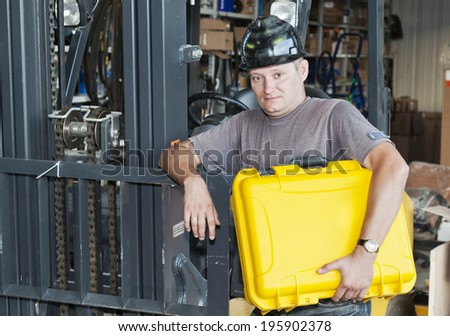 Production site. The engineer holds a yellow suitcase. - stock photo