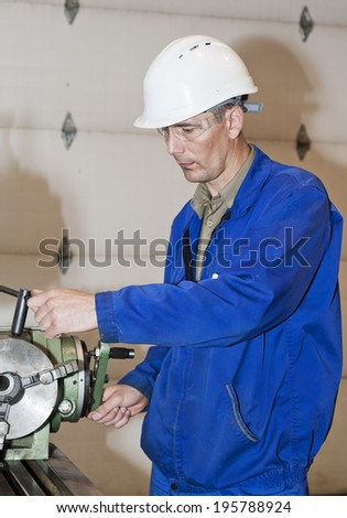 Production site. The worker using the machine. - stock photo